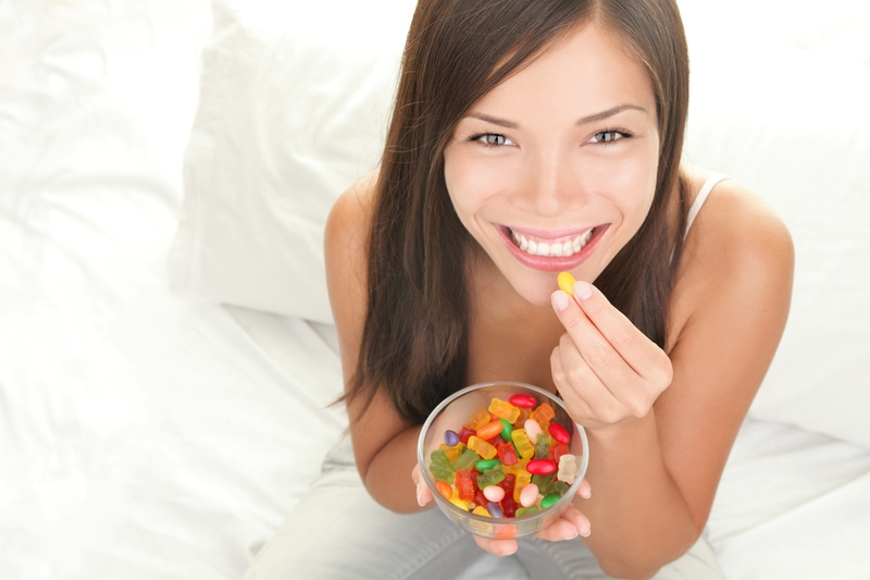 An asian, young adult woman that is eating some gummy bears from a clear bowl.