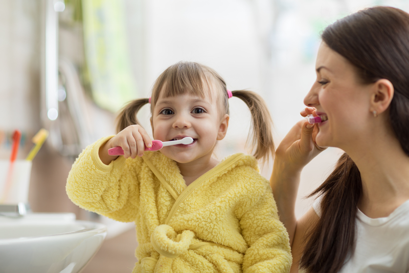 A mom brushing her teeth next to her toddler girl that is brushing her teeth and looking at the camera.