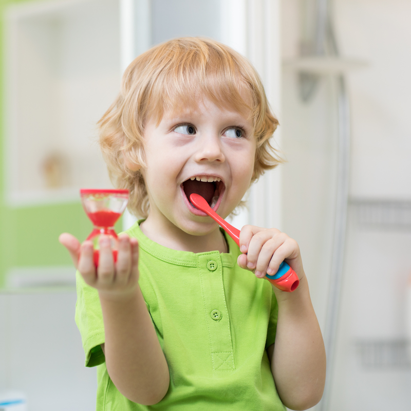 Little kid boy brushes his teeth monitoring lasting with hourglass