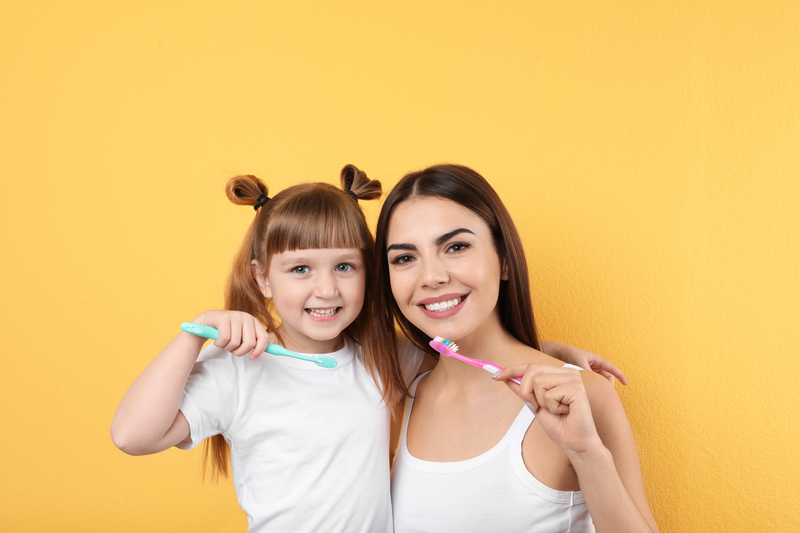 Little girl and her mother brushing teeth together on color background