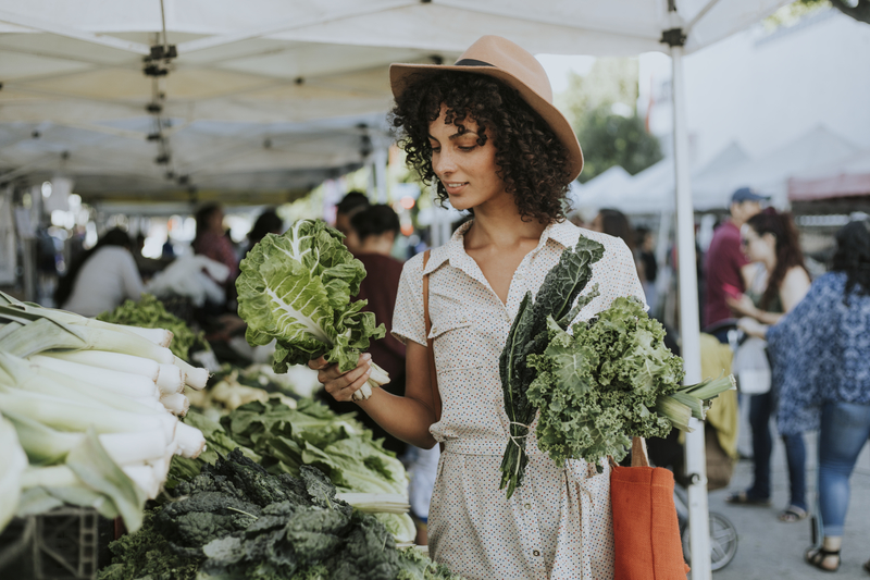 A young adult mixed-race woman that is picking up different green vegetables at a farmer's market.