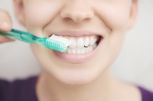 A close-up view of a woman that is brushing her teeth. Only the bottom half of her face and her toothbrush is showing.