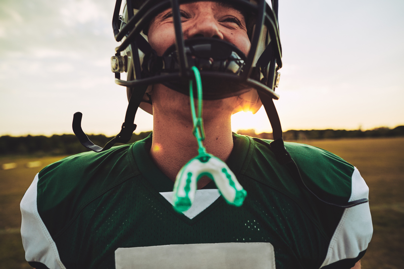 A young adult male playing football with a mouthguard and protective cage for his face.