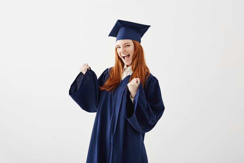 Happy cheerful graduate girl in mantle rejoicing laughing smiling over white background. Copy space.