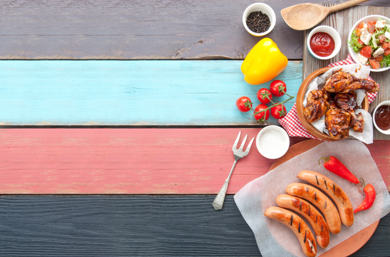 Selection of grilled barbecue meat including chicken and sausages with salad on top of a wooden table