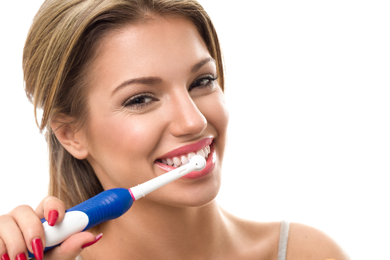 A beautiful woman that is smiling and brushing her teeth.