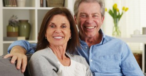 Senior couple laughing and talking to camera