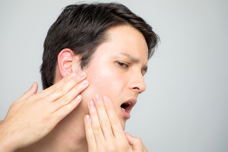 A view of a man's face as he is opening his jaw and feeling the area of his temporomandibular joint that is in pain.