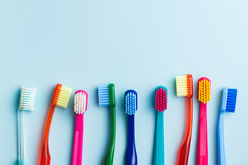 A pastel blue background that has very colorful toothbrushes lined up in front of it.
