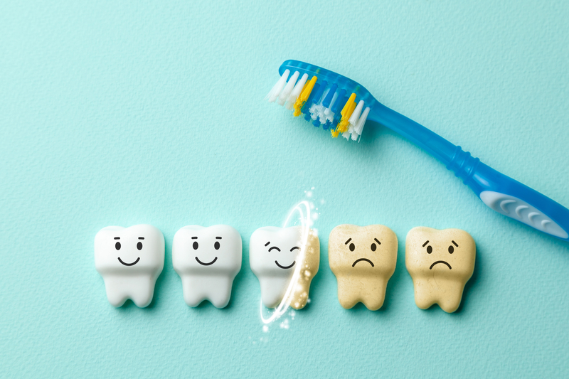 Animation of three healthy teeth and two dirty teeth with a toothbrush sitting nearby.