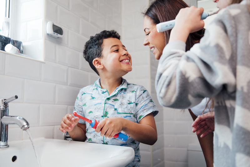 Children are brushing their teeth in the bathroom at home. The mother is checking the little boy's mouth to make sure he has brushed properly.