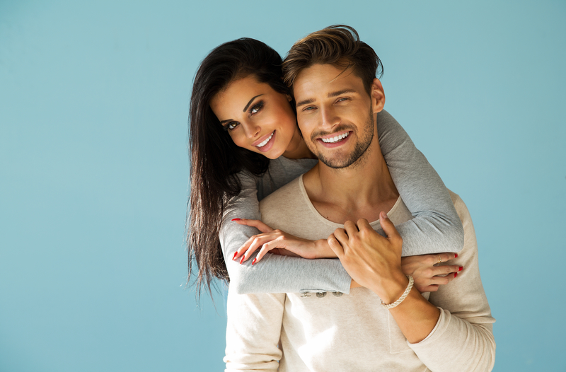 A brunette couple of a man and woman that are both very attractive with beautiful smiles.