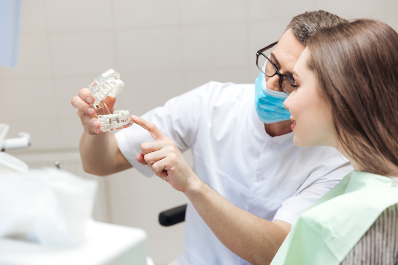 A dentist showing a patient what a dental crown looks like by using a dental model mold.