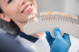 A woman patient that is being shown all the different shades of porcelain veneers she can have on her teeth.