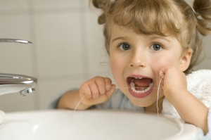 Young female child looking at the camera and flossing her teeth.