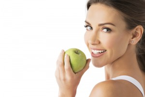 Woman smiling towards the camera as she goes to eat an apple.