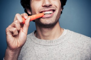 Close-up view of a male eating a carrot and smiling.