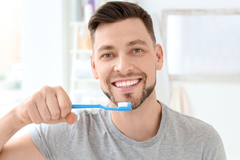 Young man brushing his teeth indoors