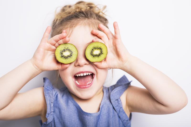 Little girl holding kiwis in front of her eyes