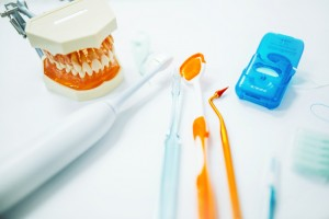 A collection of oral health products that include a toothbrush, electric toothbrush, floss, mouth model, and dental tools.