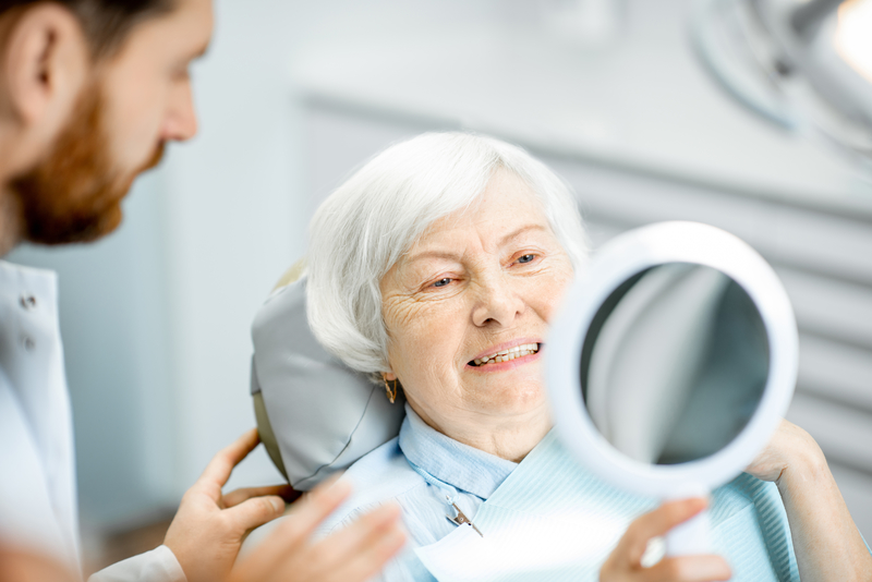 Elderly woman at the dentist smiling into a hand-held mirror
