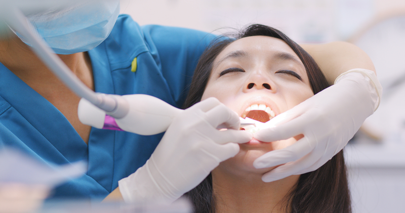 Woman receiving root planing and scaling treatment at the dental office.