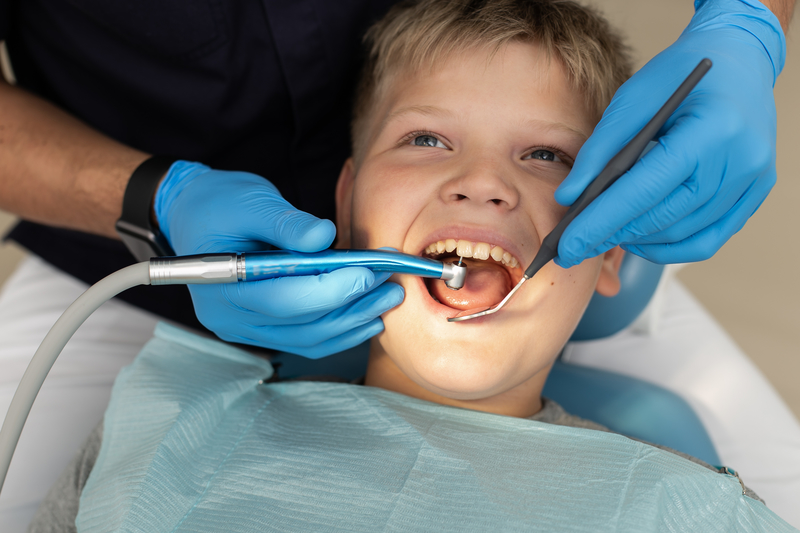 Young boy having his teeth cleaned at the dentist office.