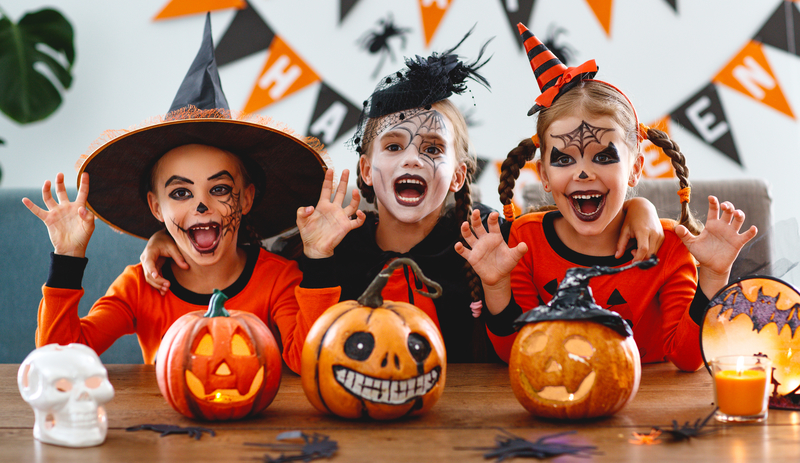 Three kids dressed up as witches with pumpkins for Halloween as they smile at the camera.