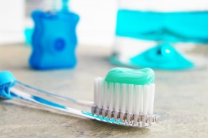 A toothbrush with toothpaste on it with floss and mouthwash in the background.