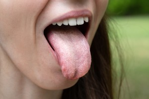 A close-up view of a woman sticking out her tongue.