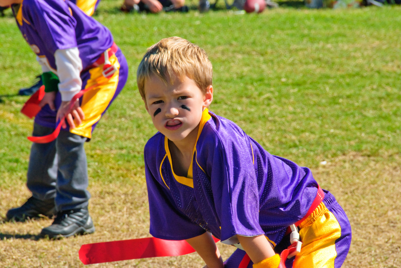 Child playing flag football but he is wearing a mouth guard to protect his teeth.