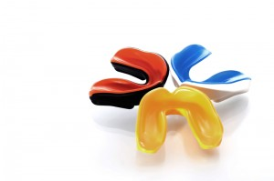 Three mouth guards together on a white backdrop. There is a red and black one, a blue and white one and a yellow one.