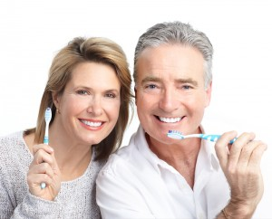 Picture of a middle-aged couple that is brushing their teeth together.