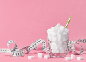 A cup full of sugar with a straw in it with sugar cubes around the cup. There is a measuring tape around the cup.