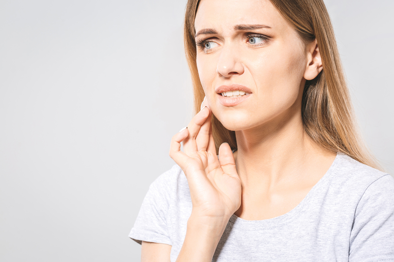 A woman that is touching the side of her mouth and has a look of pain on her face.