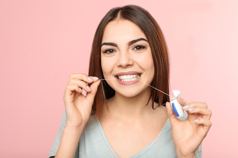 Young woman flossing teeth standing in front of a pink background.
