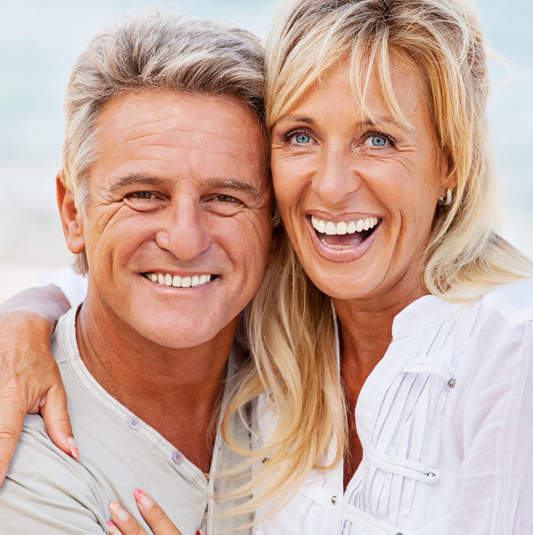 Middle-aged couple smiling with great teeth.