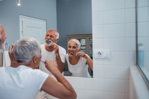 Senior citizen couple that is brushing their teeth in a mirror together.