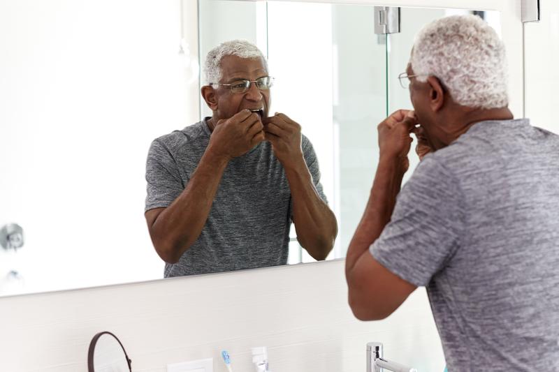 Senior Man Flossing Teeth Looking At Reflection In Bathroom Mirror Wearing Pajamas