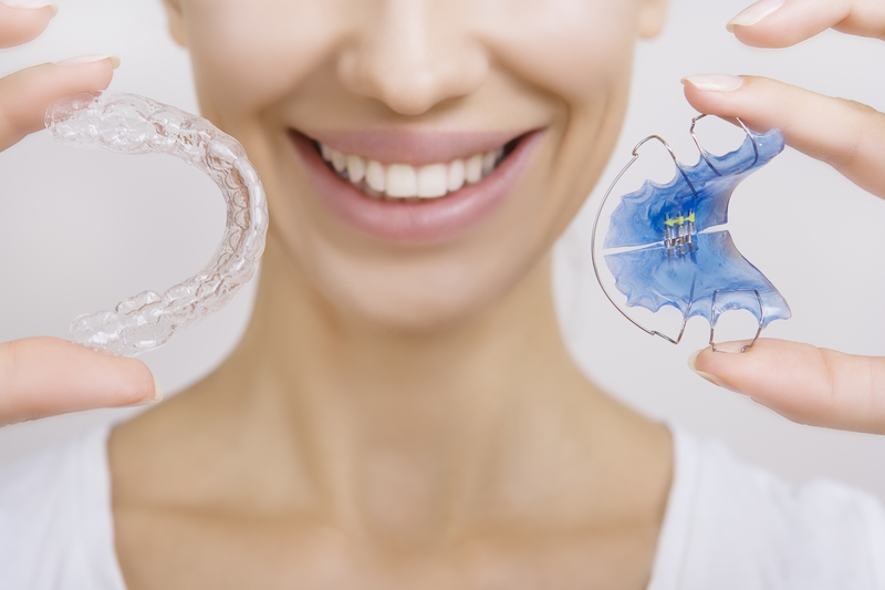 Beautiful Smiling girl Holding Retainer for Teeth (Dental Braces) and Individual Tooth Tray. Orthodontics Dental Theme, Methods of Teeth (Bite) Correction, Close-up