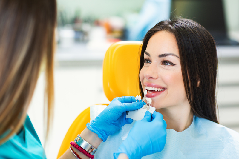 Young woman smiling in dental chair while the dentist holds different colored crowns to her teeth