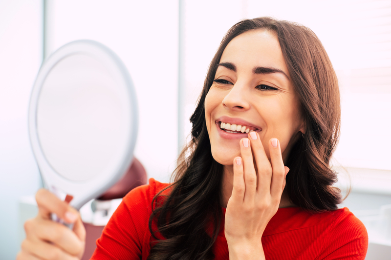 Woman looking in mirror at teeth and smiling happily.