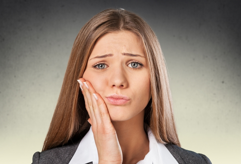 Woman that is frowning and holding her face due to a toothache.