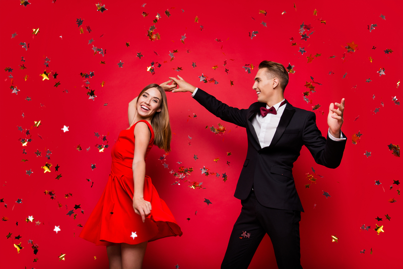 Portrait of two cool slim graceful classy elegant chic attractive cheerful positive people friends rejoicing flying decorative elements having fun isolated over bright vivid shine red background