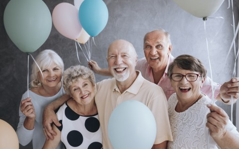 Smiling senior friends with colorful balloons enjoying meeting