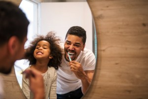 A young dad brushing his teeth in the mirror with his young daughter.
