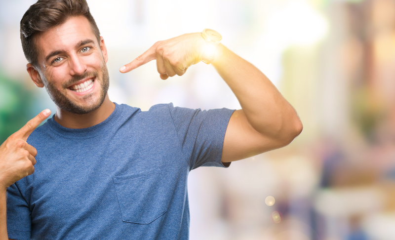 An athletic, attractive male that is smiling and pointing to his healthy smile.