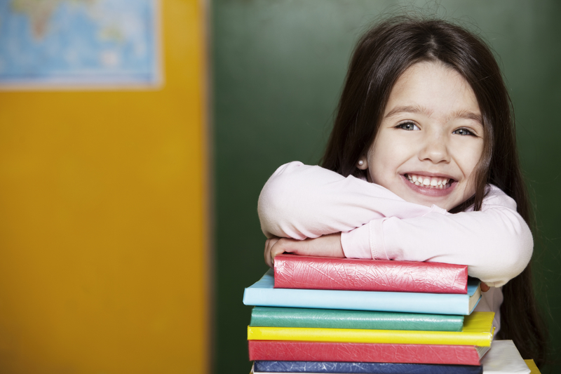 Happy little girl smiling with her arms on school books