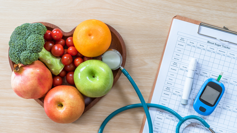 Bowl of fruit shaped in a heart alongside a clipboard that has a stethoscope and diabetic treatment equipment laying on top of it.