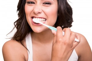 Brunette woman that is smiling and brushing her teeth with excitement.